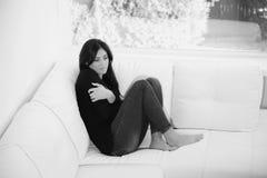 Nachdenkliche Frau, die sitzend auf Sofa sich umarmt Stockbild