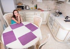 Nachdenkliche Frau, die am Tisch in der Küche sitzt Lizenzfreies Stockbild