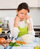 Nachdenkliche Frau kocht Reis mit Gemüse Stockfotografie