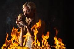 Nachdenkliche Frau mit einem Dracheei im Feuer Lizenzfreies Stockbild