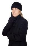 Nachdenkliche Frau mit einem schwarzen Mantel Stockbild