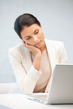 Nachdenkliche Frau mit Laptop-Computer Stockfotografie