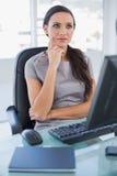 Nachdenkliche Geschäftsfrau, die auf ihrem Drehstuhl sitzt Stockbild
