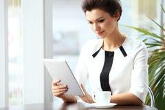 Nachdenkliche Geschäftsfrau, die einen Artikel auf Tablet-Computer liest lizenzfreies stockfoto