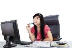 Nachdenkliche Geschäftsfrau, die im Studio sitzt Stockfoto