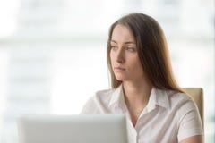 Nachdenkliche Geschäftsfrau, die an Lösung denkt Stockfotografie