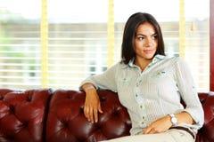 Nachdenkliche Geschäftsfrau, die am Sofa sitzt Lizenzfreie Stockfotografie