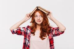 Nachdenkliche Ingwerfrau im Hemd, das Buch auf ihrem Kopf hält lizenzfreie stockbilder