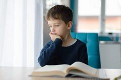 Nachdenkliche 8 Jahre alte Junge, die seine Hausarbeit am Tisch tun stockbild