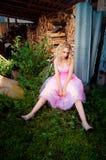 Nachdenkliche junge blonde Frau im rosafarbenen Kleid Stockbilder