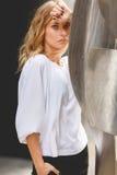 Nachdenkliche junge blonde Frau mit der Hand, die ihre Stirn berührt Lizenzfreies Stockfoto