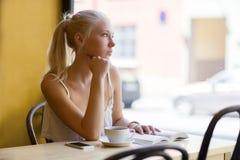 Nachdenkliche junge Frau am Café schaut heraus das Fenster Stockfotografie