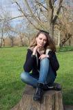 Nachdenkliche junge Frau, die auf einem alten Baumstumpf sitzt Stockbilder