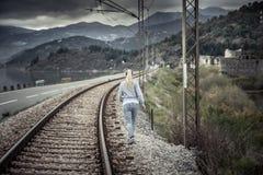 Nachdenkliche junge Frau, die in den Abstand über Bahnweg am bewölkten Tag mit dem drastischen Himmel symbolisiert die Trennung u stockbilder