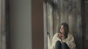 Nachdenkliche junge Frau, die durch ein Fenster schaut stock video footage
