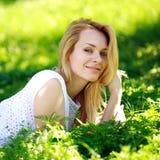 Nachdenkliche junge Frau, die im grünen Gras, Sommertag genießend liegt Lizenzfreie Stockbilder