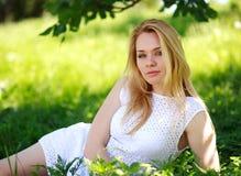 Nachdenkliche junge Frau, die im grünen Gras, Sommertag genießend liegt Stockfotografie