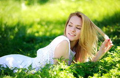 Nachdenkliche junge Frau, die im grünen Gras, Sommertag genießend liegt Stockfotos