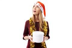 Nachdenkliche junge Frau, einen Santa Claus-Hut tragend, Träume und schauen stockfotos