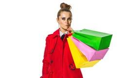 Nachdenkliche junge Frau im roten Mantel auf Weiß mit Einkaufstaschen lizenzfreie stockfotos