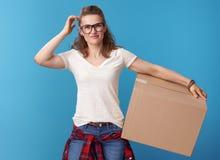 Nachdenkliche junge Frau im weißen Hemd mit Pappschachtel auf Blau lizenzfreie stockfotos