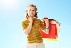 Nachdenkliche junge Frau mit Einkaufstaschen gegen blauen Himmel stockfotografie