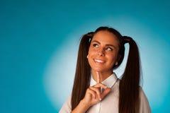 Nachdenkliche junge hispanische Frau, die vor blauem Hintergrund denkt Lizenzfreie Stockfotografie