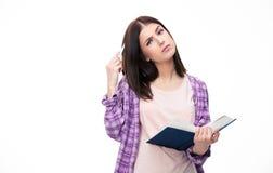 Nachdenkliche junge Studentin, die mit Buch steht Stockbild