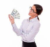 Nachdenkliche lächelnde Brunettegeschäftsfrau mit Geld Lizenzfreies Stockfoto