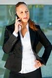 Nachdenkliche moderne Geschäftsfrau, die auf Mobile spricht Lizenzfreie Stockfotografie