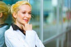 Nachdenkliche moderne Geschäftsfrau nahe Bürohaus Stockbild