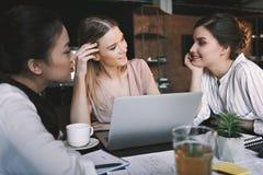Nachdenkliche multikulturelle Geschäftsfrauen, die Projekt im Café bearbeiten und besprechen Lizenzfreies Stockbild