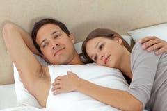 Nachdenkliche Paare, die in den jeder des anderen Armen liegen Stockbilder