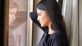 Nachdenkliche recht deprimierte junge Frau, unten schauend Stockfotografie