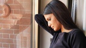 Nachdenkliche recht deprimierte junge Frau, unten schauend Stockfoto