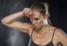 Nachdenkliche sportliche Frau mit der Hand auf Stirn Lizenzfreie Stockfotografie