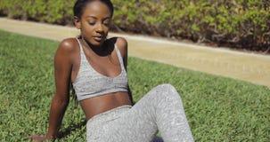 Nachdenkliche sportliche schwarze Frau im Park stock footage
