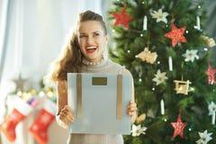 Nachdenkliche stilvolle Frau mit Gewichtsskalen nahe Weihnachtsbaum lizenzfreie stockbilder