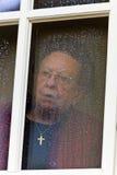 Nachdenklicher Älterer schaut von einem Fenster traurig Lizenzfreies Stockbild