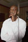 Nachdenklicher afrikanischer Mann in einem dunklen Büro Lizenzfreies Stockfoto