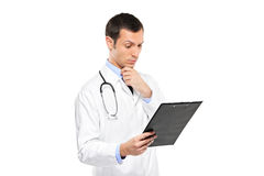 Nachdenklicher Arzt, der Klemmbrett betrachtet Stockfotografie