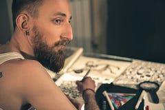 Nachdenklicher bärtiger Mann, der Bilder schafft Stockfotos