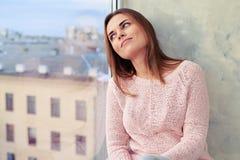 Nachdenklicher Blick der Frau beim Sitzen auf einem Fensterbrett und Schauen von O Stockfotografie