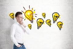 Nachdenklicher blonder Geschäftsmann und viele Ideen Stockfotos