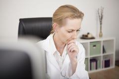 Nachdenklicher blonder weiblicher Kliniker, der unten schaut Stockfoto