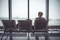 Nachdenklicher einsamer Frauentourist im Flughafenabfertigungsgebäude, das auf Stuhl sitzt und auf Flugzeugen durch Fenster in de Lizenzfreies Stockbild