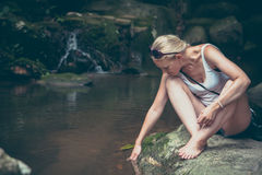 Nachdenklicher entspannender nahe gelegener Gebirgsfluss der jungen Frau nachdem dem Wandern in der Retro- Weinleseart Lizenzfreie Stockbilder