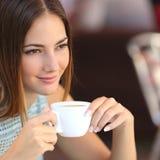 Nachdenklicher Frauenprobierenkaffee in einem Restaurant Stockfoto