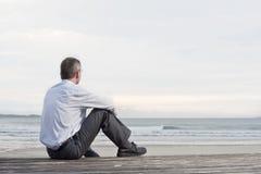 Nachdenklicher Geschäftsmann, der in dem Meer sitzt Stockbild