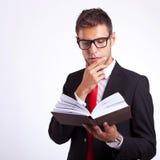 Nachdenklicher Geschäftsmann, der ein Buch liest Stockbilder